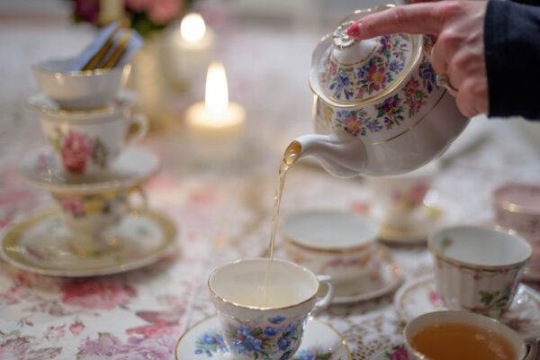 woman pouring tea into vintage tea cup on table inside for adult tea party